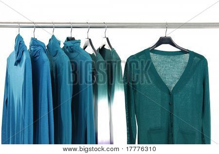 Blue knitted female jacket on a rack on black hangers