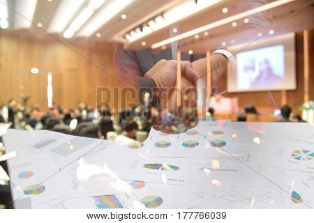 Double Exposure Of Businessman Handshake Over Blurred Image Of Conference Hall Or Seminar Room With