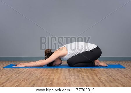Young asian woman practicing yoga pose at yoga healthy sport gym yoga and meditation have good benefits for health. Photo concept for Yoga Sport and Healthy lifestyle.