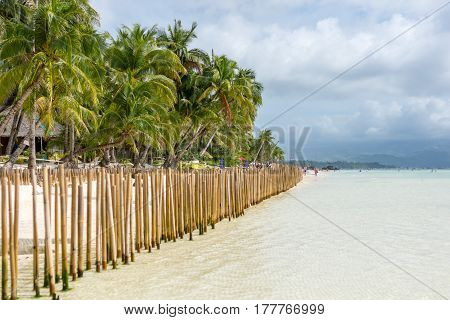 Looking down a fence barrier made of bamboo poles in a tropical island white sand beach with a palm tree lined shore and hilly headland in the distance.