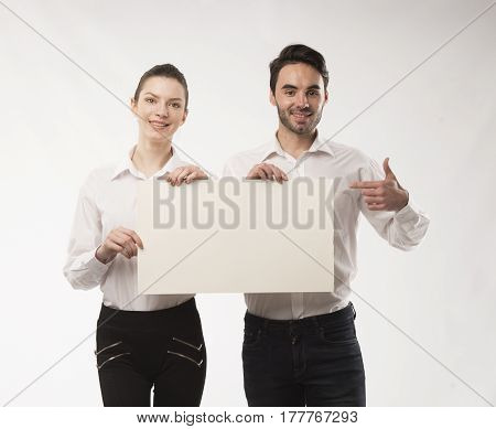 Young happy couple portrait of a confident businessman showing presentation, pointing on paper placard over gray background. Ideal for banners, registration forms, presentation, landings, presenting concept.