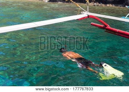 Young man snorkelling swimming with mask and flippers along side a Filipino pump boat.