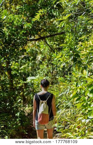 Black haired young woman walking along a path through a thick green jungle with canvas back pack on sunny day.