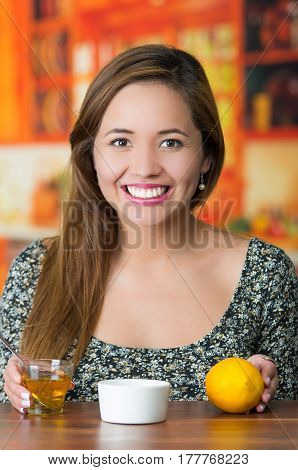 Young brunette model sitting by table smiling, small glass of hooney and a lemon in front.