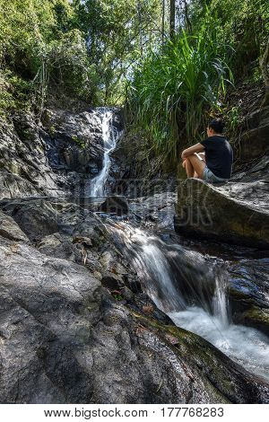 Young woman sat on rocks looking at a jungle waterfall contemplating.