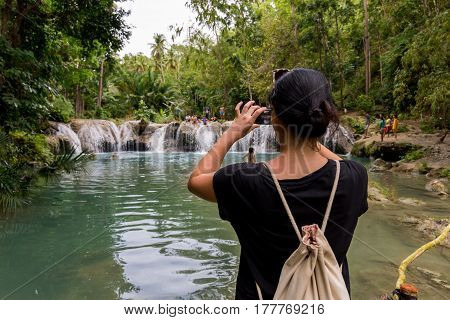 Young women using her smart phone to photograph local children playing at waterfall surrounded by thick rainforest.
