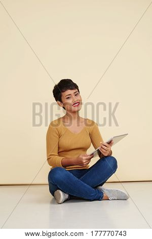 Pretty young woman sitting on the floor with digital tablet
