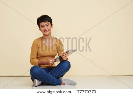 Joyful Filipino woman with tablet sitting on the floor with digital tablet