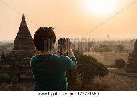 Female traveler photographing ancient pagoda at Bagan Myanmar at sunrise