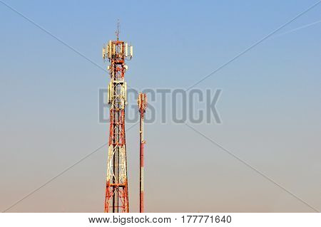 Antenna repeater tower for mobile phones with a blue sky. Antenna for mobile signal near city.