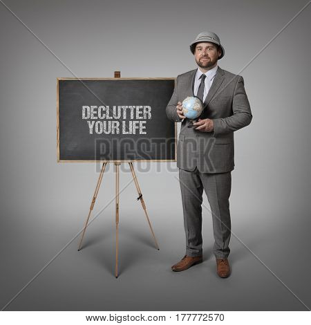 Declutter your life text on blackboard with businessman holding globe in hands