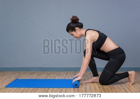 Young Asian Woman Preparing Yoga Mat For Practicing Yoga At Yoga Healthy Sport Gym. Yoga And Meditat