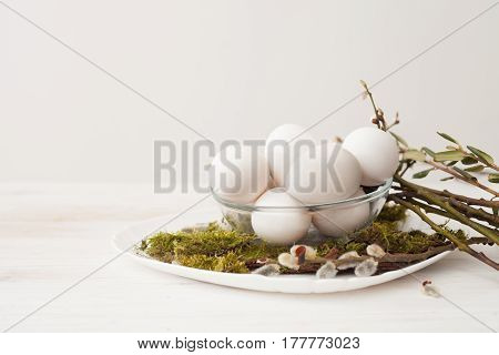 Eggs Lie On The Plate, Moss Green, Willow Branches Of Willow, Eggs In Glass Cup, On A White Backgrou