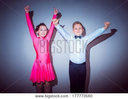 The young boy and girl posing at dance studio on gray. The ballroom dancing concept. Winners
