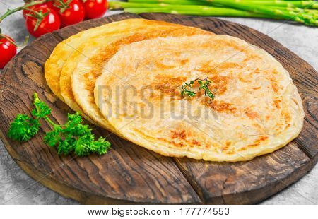 Stack of not sweet frying flour Flatbread Paratha roti tortillas. Ingredients for Flatbread Paratha roti cherry tomatoes asparagus parsley wooden board served on light gray background.