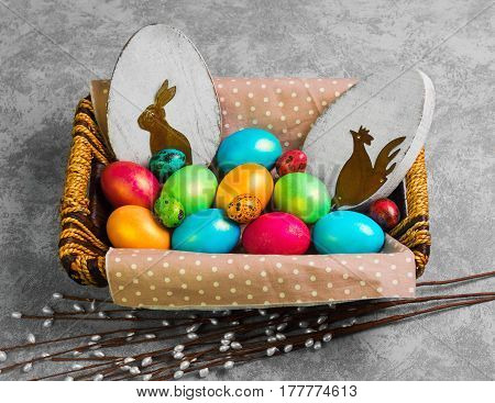 Easter card. Painted eggs of chicken and quail in a basket. Sprigs of the Easter willow. Wooden eggs with an Easter bunny and chicken. Gray concrete background.