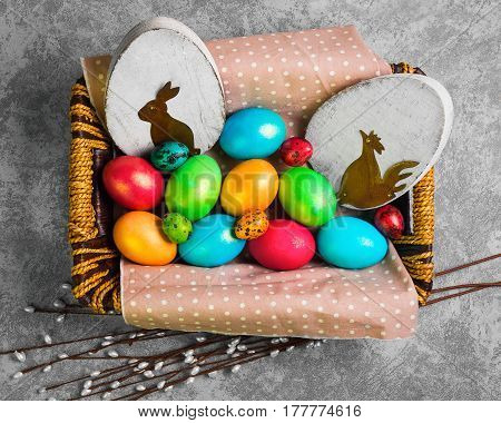 Easter card. Painted eggs of chicken and quail in a basket. Sprigs of the Easter willow. Wooden eggs with an Easter bunny and chicken. Gray concrete background. Top view from above and copy space