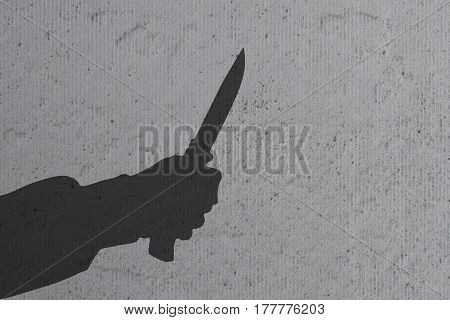 Humans hand with knife silhouette in shadow on concrete wall background with space for text or image.