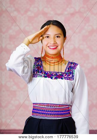 Young woman wearing traditional andean dress, facing camera doing sign language word for goodbye.