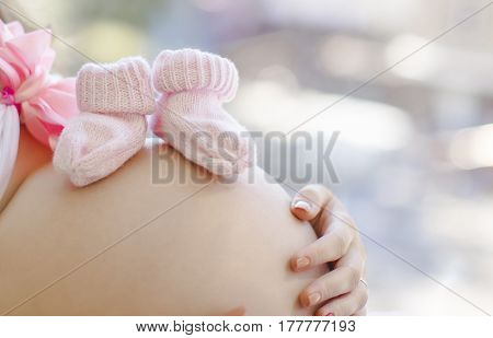 Pregnant  woman baby's bootee hands baby bump