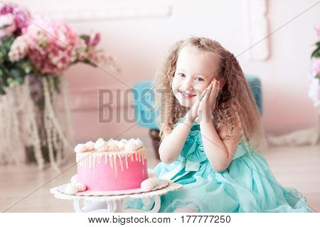 Cute kid girl 3-4 year old sitting with cake in room. Birthday party. Childhood.
