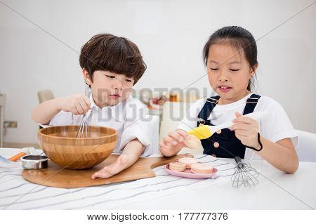 Asian Chinese Little Brother And Sister Preparing To Bake Cookies