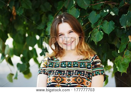 Happy smiling woman on green foliage background. Shallow depth of field. Selective focus.