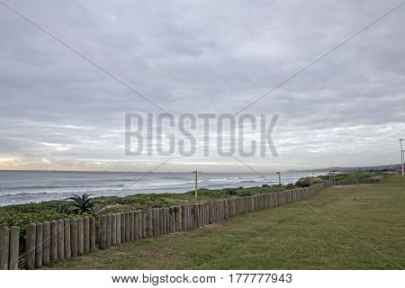 Green Lawn And Wooden Pole Barrier Fence On Beachfront