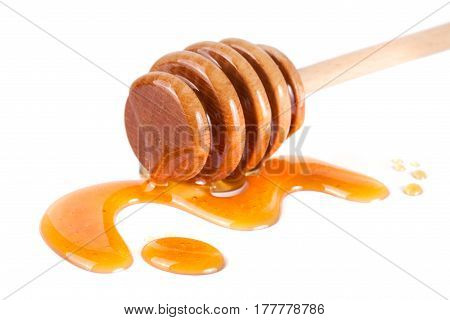 Honey stick with flowing honey isolated on white background.