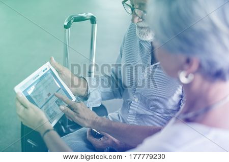 Senior adult couple checking boarding pass on digital tablet
