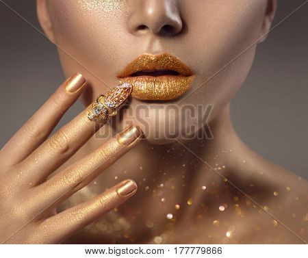 Fashion art Golden skin Woman face portrait closeup. Beauty gold nail ring, Lips and Skin. Model girl perfect make up. Glamour shiny professional makeup with shiny sparks on her lips and body
