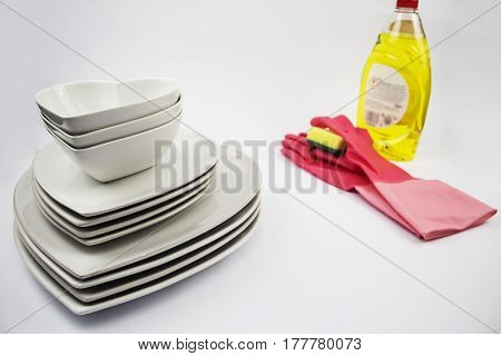 A concept of no more dirty dishes with clean heart shaped plates and bowls with washing up liquid sponge and gloves in the background