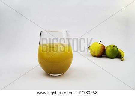 A glass of fresh orange juice with ice with fruit in the background