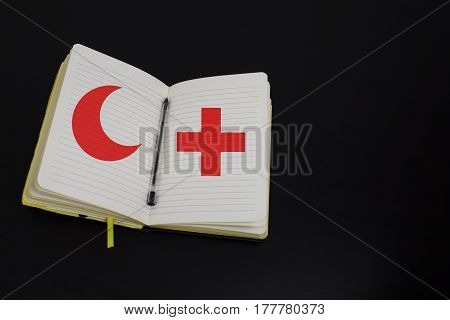 A lined notebook with pen resting on a table with a red cross and red crescent