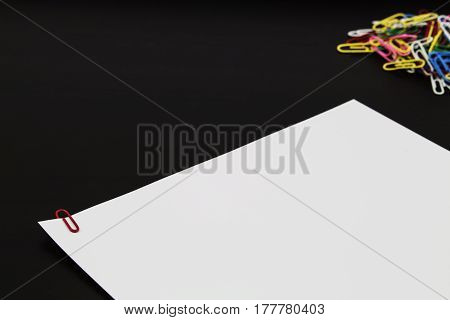 A red paperclip being used to hole paper together with a pile of paperclips in the background