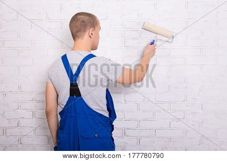 Rear View Of Young Man Painter In Workwear Painting Brick Wall With Paint Roller