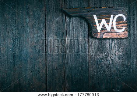 Pointer of old dark wood with text 'WC' on wooden wall or door. Close-up view