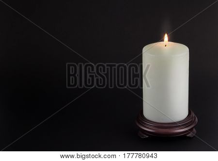 One white lit candle on wood stand isolated on black background