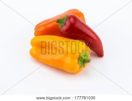 Three sweet orange red and yelllow peppers on white background