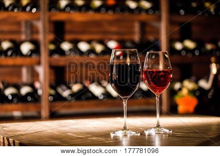 Two glasses filled with wine placed on the wooden table in fromt of the shelves with wine bottles.