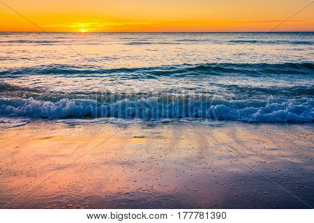 Waves and sunset over sea at Glenelg Beach South Australia