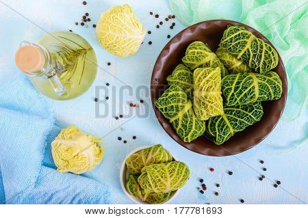 Leaves of Savoy cabbage stuffed with minced meat and rice in a clay bowl on a light background. Top view.