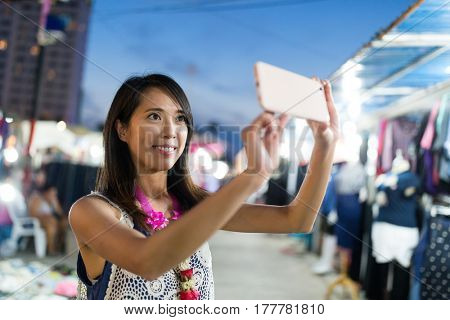 Woman taking selfie at night market in thailand