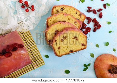 Soft festive fruitcake with raisins and dried cranberries decorated with sugar icing cut by pieces on a light background. Top view.