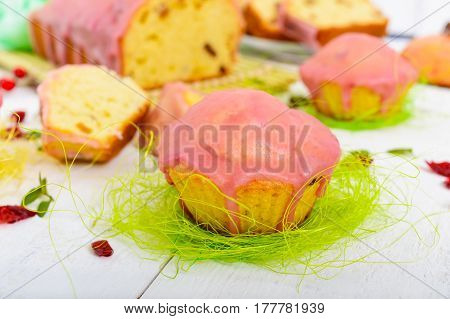 Soft festive fruitcake with raisins and dried cranberries decorated with sugar icing on a light background.