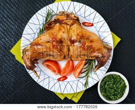 Baked rabbit legs on a plate on a black background. The top view