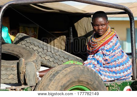 MARARAL KENYA - JULY 03: African woman from the Samburu tribe with characteristic decorative necklaces is waiting for the transport by jeep to one's village in the bushon near the Mararal town in Kenya Mararal in July 03 2013