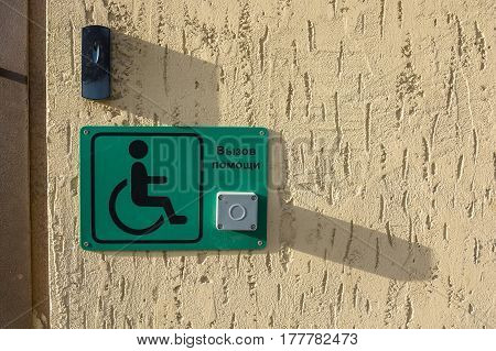 Close up of green plastic tablet with signal button for the disabled people hanging at entrance with Russian inscription call for help