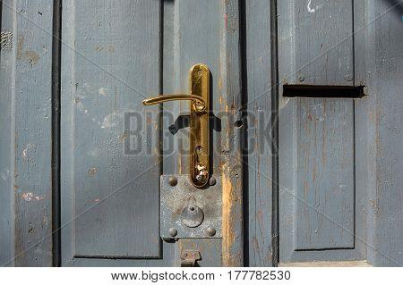Close-up of obsolete golden door handle on grey wooden entrance door