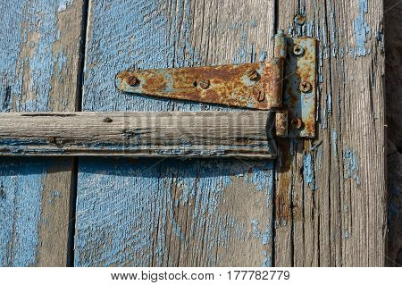 Close-up old rusty door hinge on weathered blue wooden door